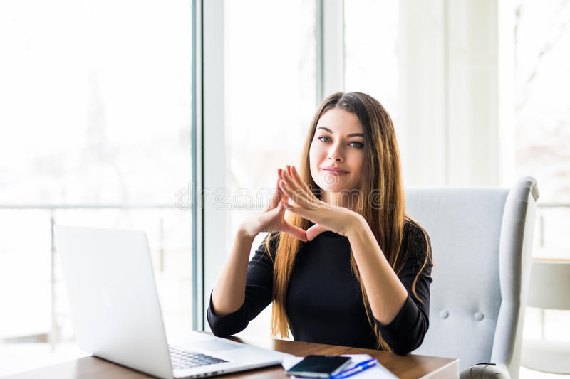 Young beautiful businesswoman working on laptop and keeping hand on chin while sitting at her working place. Searching for new solution. Pensive young beautiful royalty free stock images