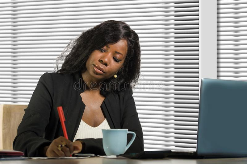 Young beautiful and busy black African American businesswoman writing notes on desk working with laptop computer at company office. Corporate business portrait stock photos