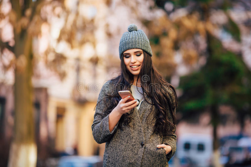 Young beautiful casual girl texting on her cell phone on spring city street stock photo
