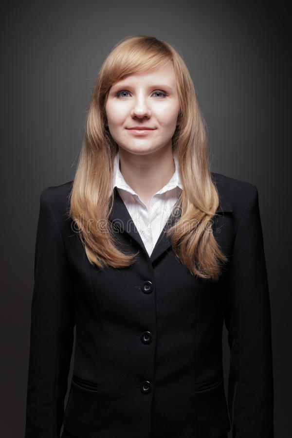Young beautiful Caucasian business woman with blue eyes head and shoulders studio shot on gray background. Looking at camera. stock images