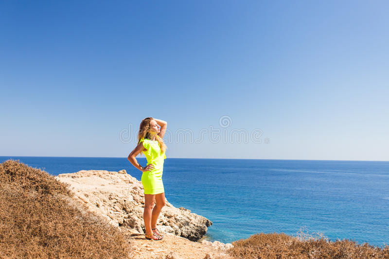 Young beautiful caucasian female on a cliff above the sea.  royalty free stock photo