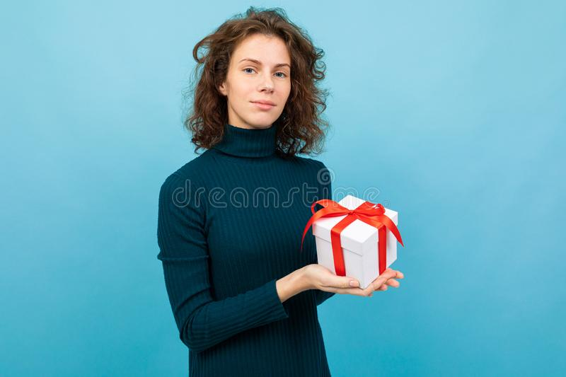 Young and beautiful caucasian girl with curly hair keeps white gift box with red ribbon and smiles, portrait isolated on stock image