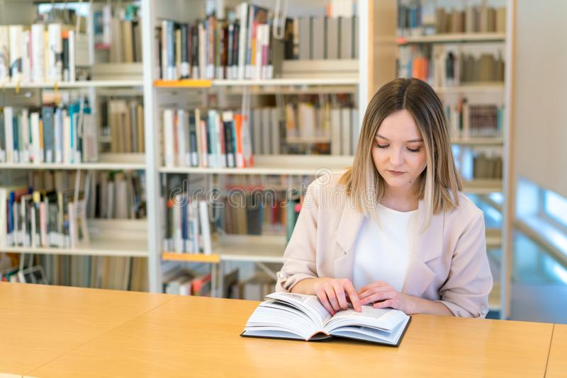 Young beautiful caucasian girl reading a book in the library pointing with her finger royalty free stock images
