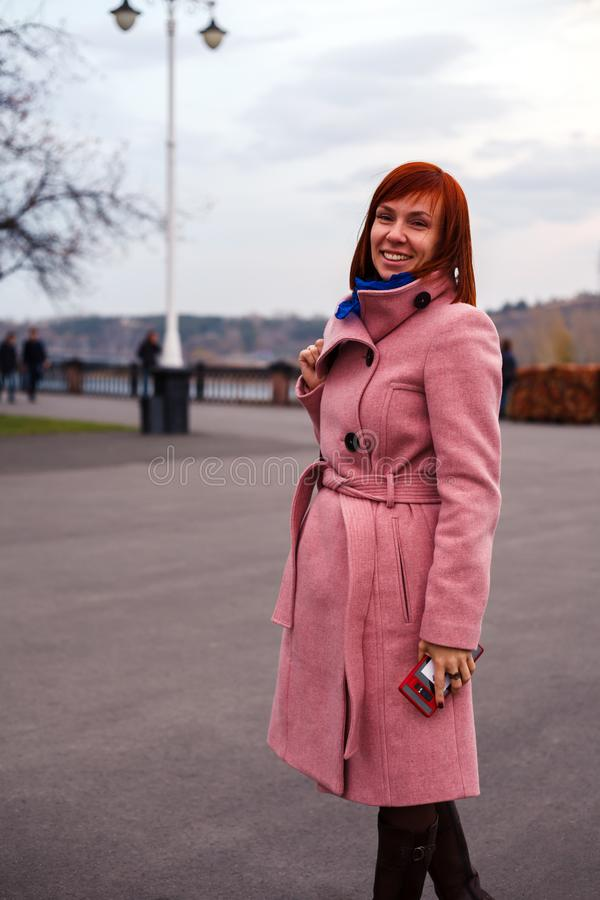 Young beautiful caucasian girl with red hair, in a pink coat wit stock photo