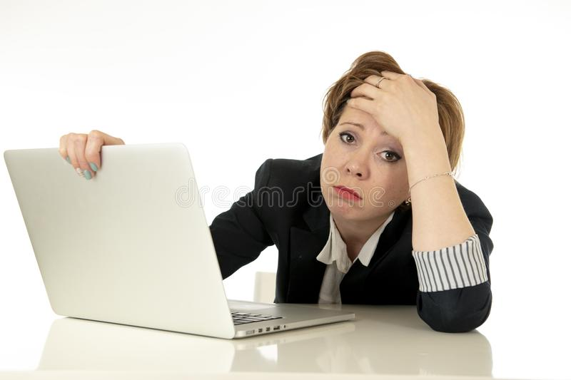 Attractive young business woman working on her computer stressed, tired and overwhelmed. royalty free stock photography