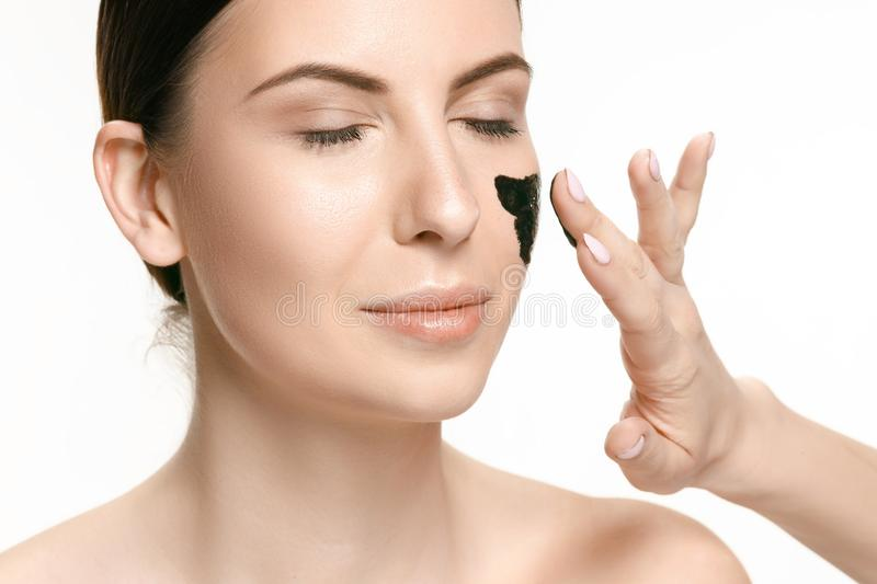 Young beautiful woman applying a mask for the face of the therapeutic black mud. Spa treatment stock photography