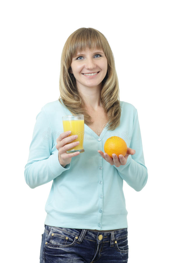 Young beautiful Caucasian woman with blue eyes waist up studio shot on white background (isolated). Looking at camera and smiling. Holding a glass of orange royalty free stock photography