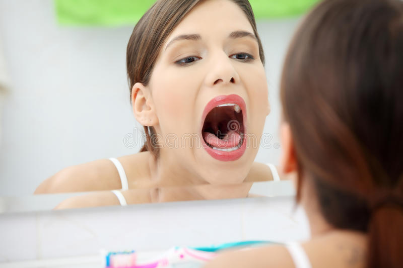 Young beautiful caucasian woman checking throat stock image