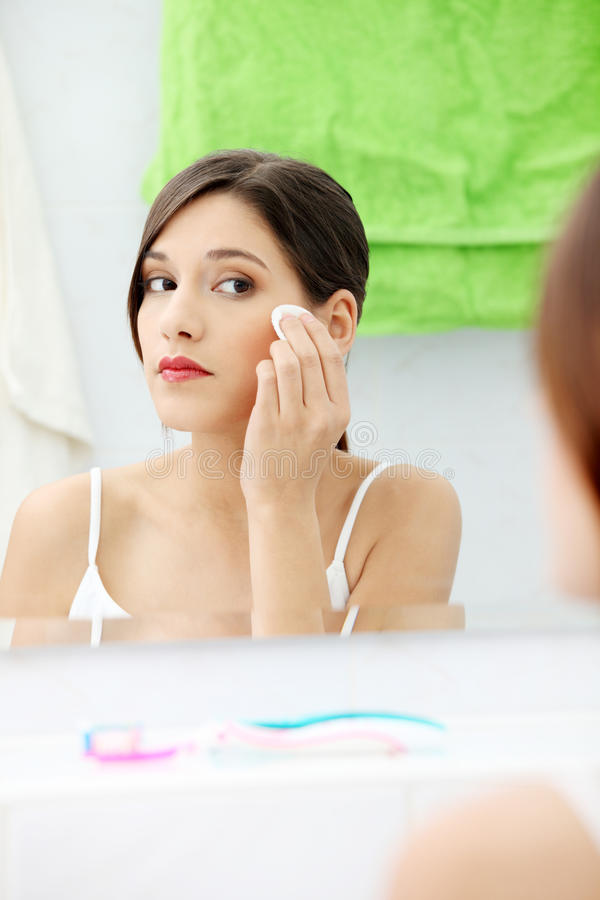 Young beautiful caucasian woman cleaning her face stock photography