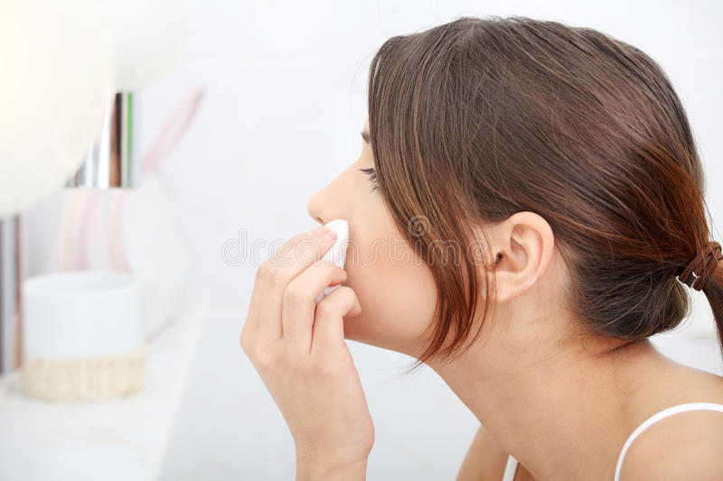 Young beautiful caucasian woman cleaning her face stock images