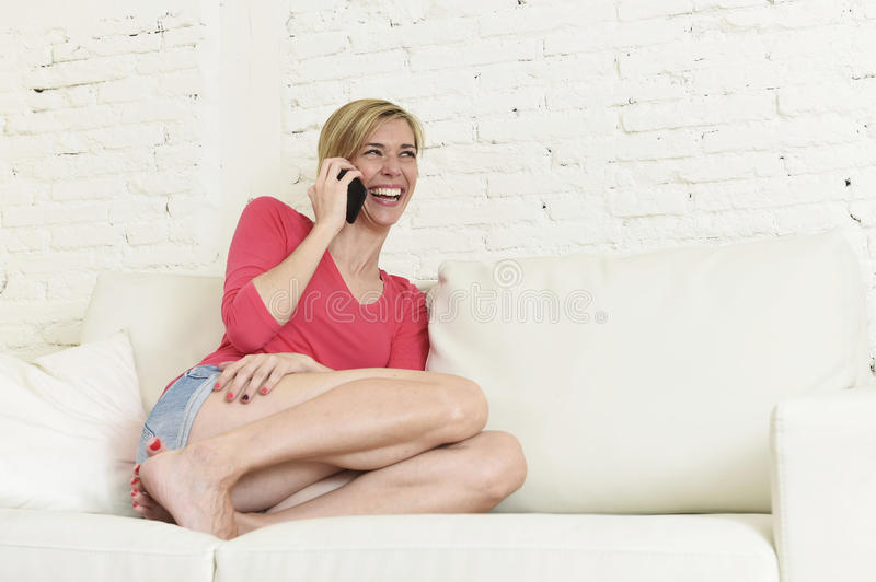 Young beautiful Caucasian woman happy on couch talking on mobile phone relaxed cheerful laughing stock photos