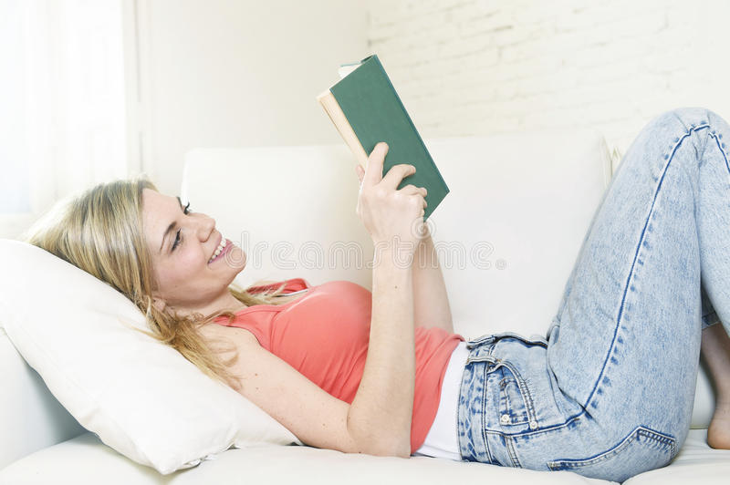 Young beautiful caucasian woman reading book studying lying comfortable on home sofa looking happy stock image