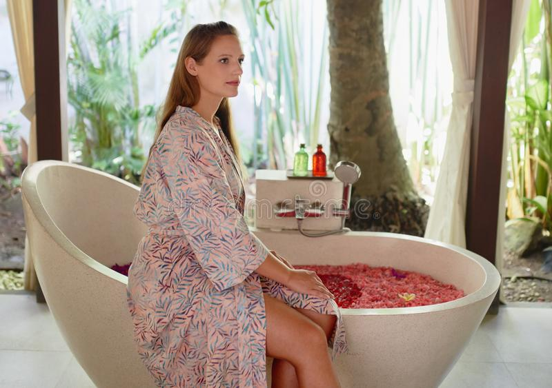 Closeup of gorgeous caucasian millennial woman relaxing at tropical hotel spa with serene herbal bath and flower stock photo
