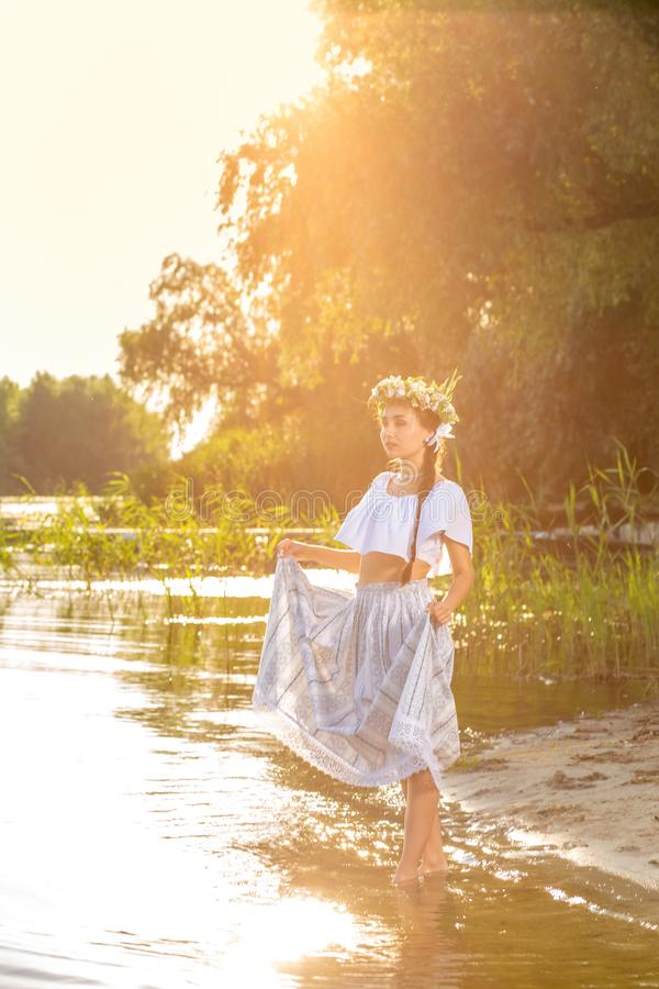 Young beautiful caucasian woman standing at the bank of river. Traditional countryside picture with girl at foreground stock photo