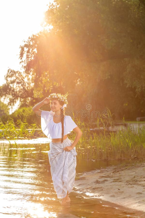 Young beautiful caucasian woman standing at the bank of river. Traditional countryside picture with girl at foreground stock photos