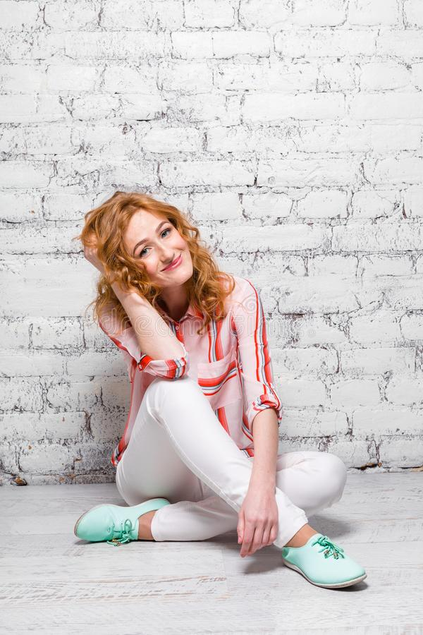 Young beautiful caucasian woman student is sitting on the floor near a white brick wall. Girl with red long curly hair stock photos