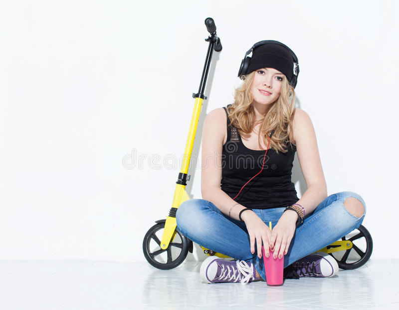 Young beautiful cheerful fashion girl in jeans, sneakers, hat sits on a yellow scooter and listening to music on headphones. Keeps. Cool pink glass in hand royalty free stock photography