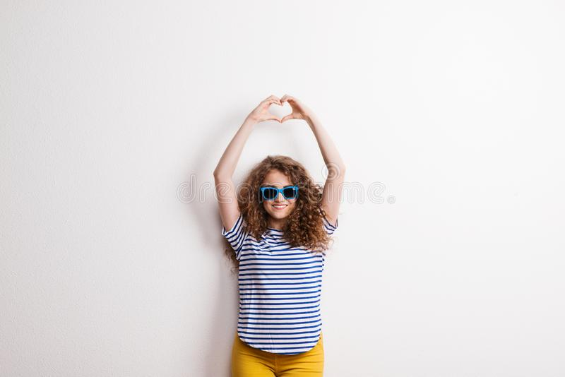Young beautiful cheerful woman with sunglasses in studio, hands forming heart. Young beautiful cheerful woman with blue sunglasses in studio, forming heart with royalty free stock image