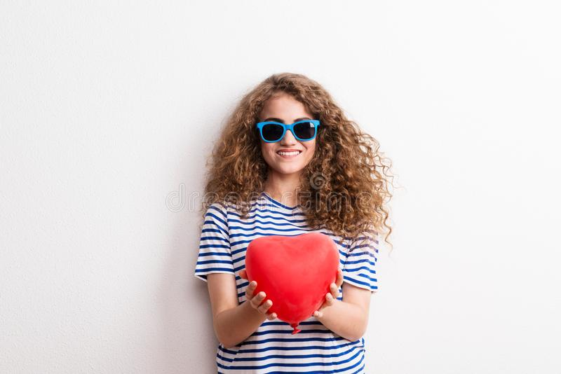 Young beautiful cheerful woman with sunglasses in studio, holding red heart. royalty free stock images
