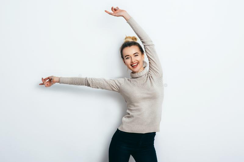 Young beautiful cheerful woman with hair bun wearing in jeans and sweater dancing and posing over white wall. Good mood. Hands up! royalty free stock image