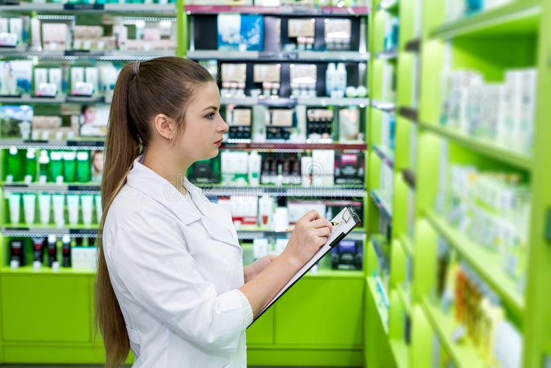 Young and beautiful chemist checking drugs in pharmacy royalty free stock photography