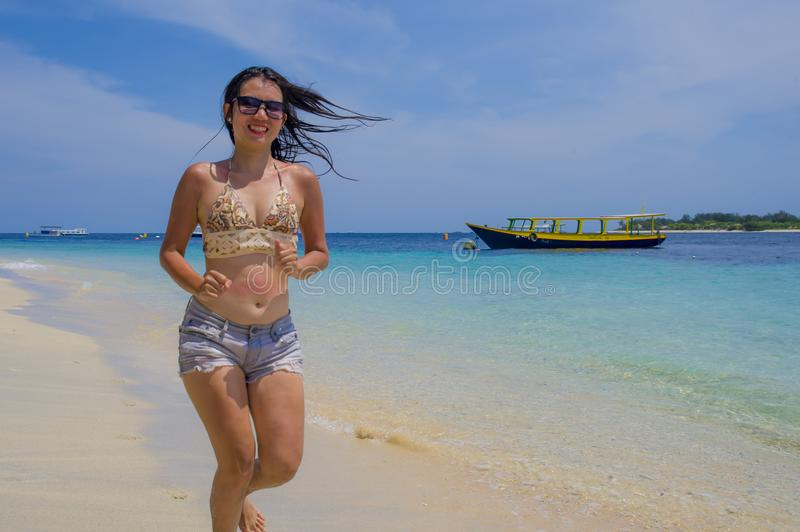Young beautiful Chinese Asian girl in shorts and bikini running on beach sand with amazing beautiful turquoise sea water color en stock photos