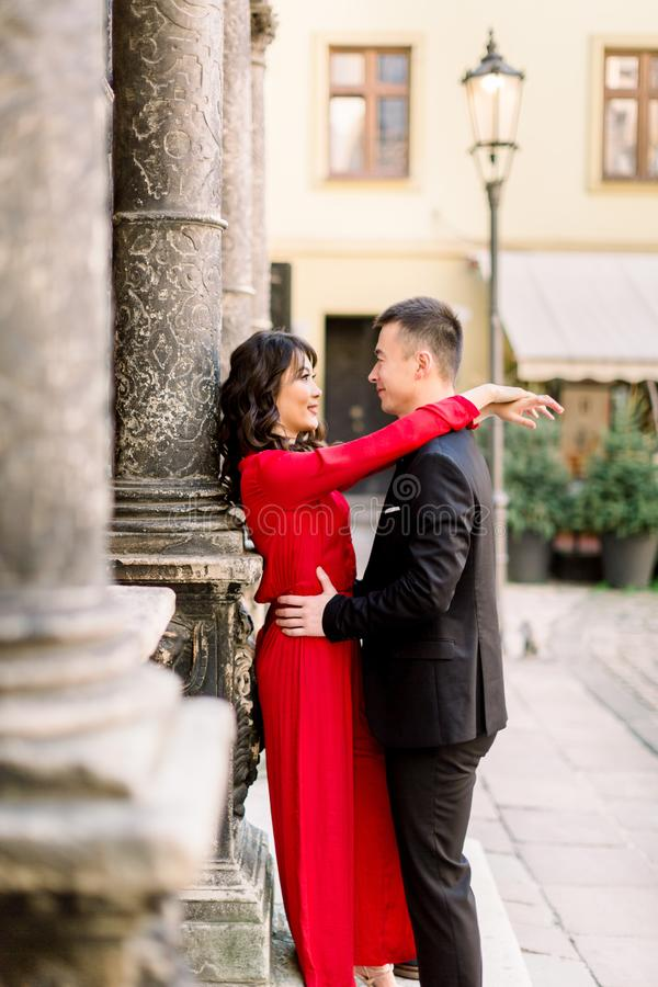 Young beautiful Chinese couple in love hugging each other on old city street, summer Europe vacation, travel, fun, happy royalty free stock photography