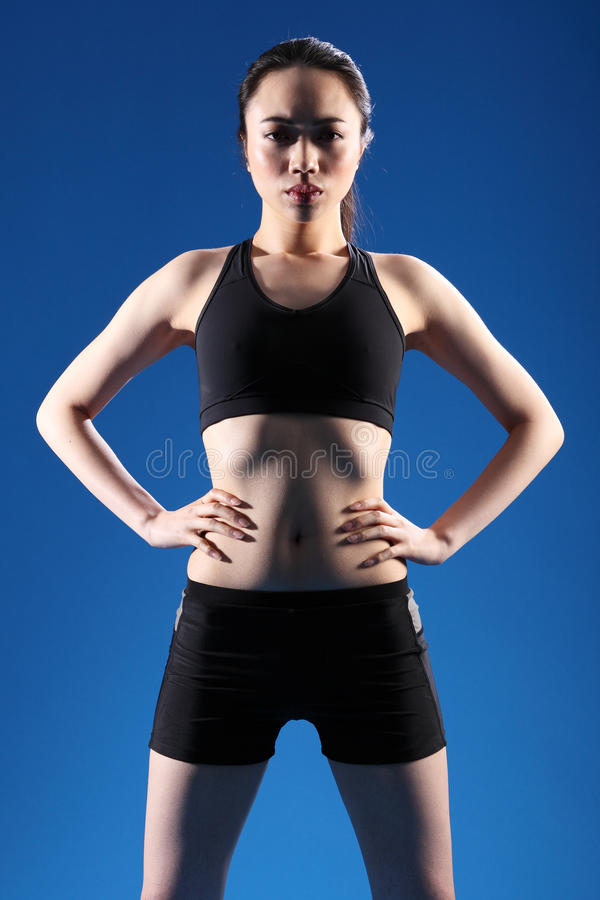 Young beautiful Chinese girl in fitness clothes. Fitness with attitude by beautiful young Chinese girl wearing black sports bra and shorts, standing in blue stock images