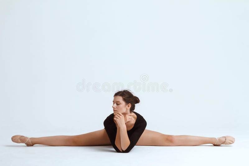 Young beautiful contemporary dancer posing over white background. Copy space. Young beautiful contemporary brunette dancer posing over white background. Copy royalty free stock image