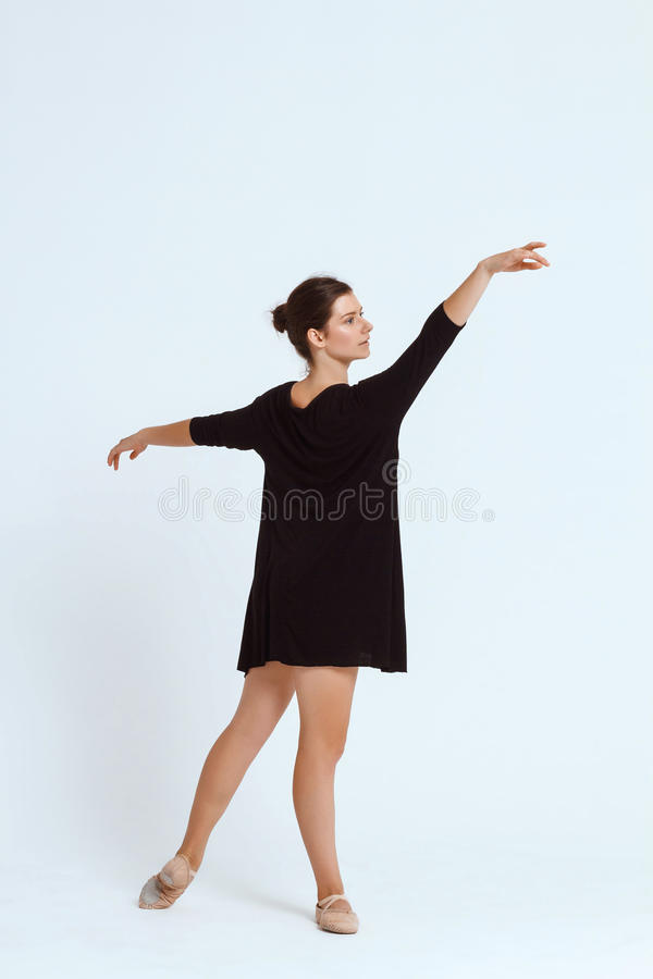 Young beautiful contemporary dancer posing over white background. Copy space. Young beautiful contemporary brunette dancer posing over white background. Copy stock images