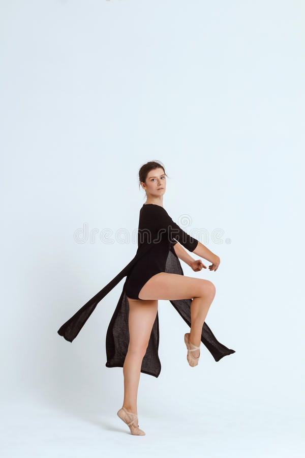 Young beautiful contemporary dancer posing over white background. Copy space. Young beautiful contemporary brunette dancer looking at camera, posing over white stock photo