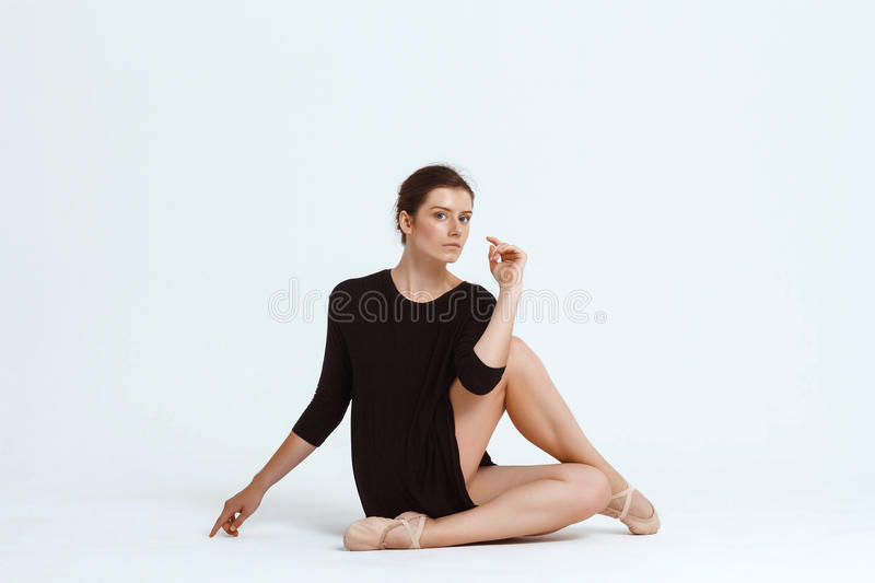 Young beautiful contemporary dancer posing over white background. Copy space. Young beautiful contemporary brunette dancer looking at camera, posing over white royalty free stock photography