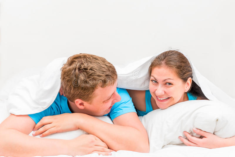 Young beautiful couple in bed royalty free stock images