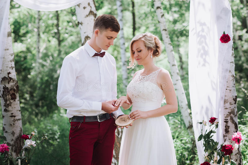 Young beautiful couple, bride and groom in the forest. Against the background of the wedding decor. royalty free stock images