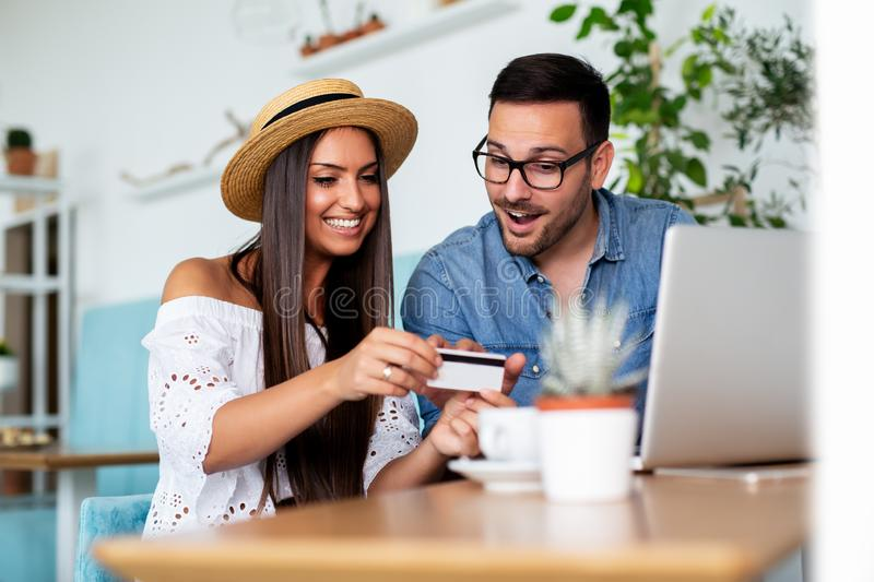 Young couple buying online with credit card and laptop in a coffee shop. - Image royalty free stock photo