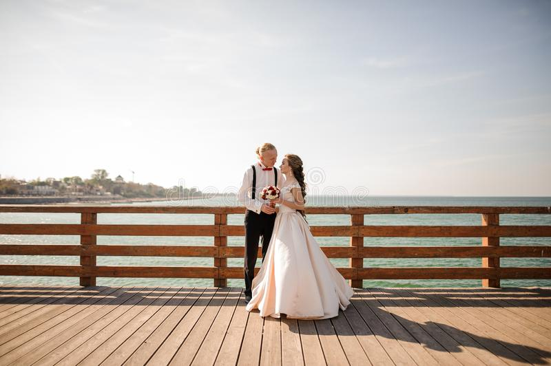 Young beautiful couple embracing on the wooden bridge in background of the sea royalty free stock photo