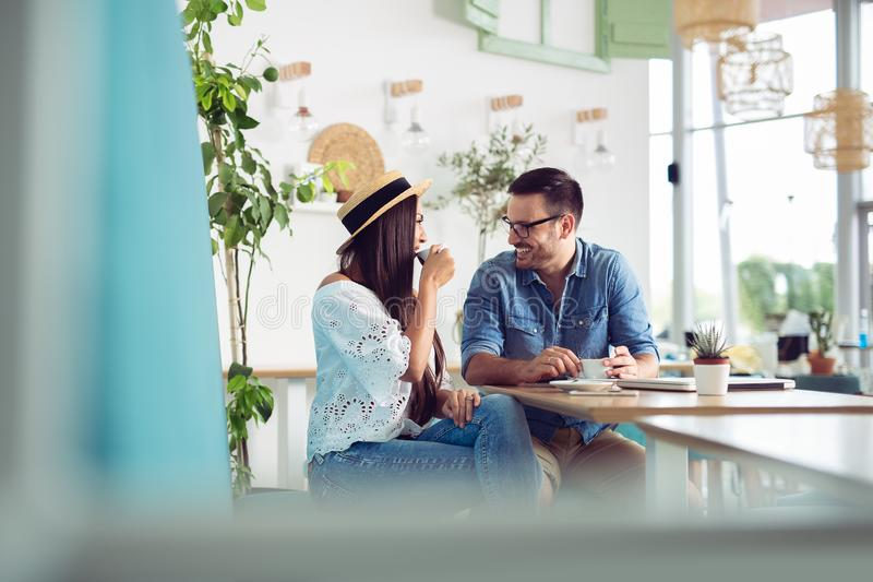 Young couple enjoying restaurant and drinking coffee royalty free stock photography