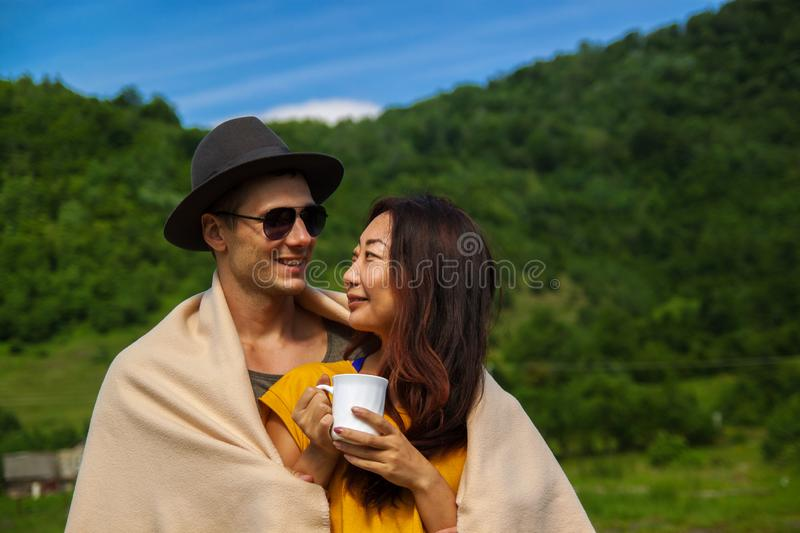 Young beautiful couple in the forest enjoy nature and drink tea. Young beautiful couple of different nationalities in the forest enjoy nature and drink tea stock images