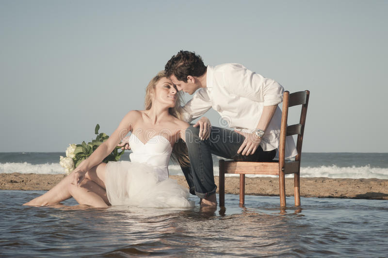 Young beautiful couple hanging out together at the beach. Sitting in body of water royalty free stock photography