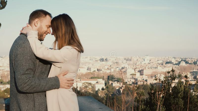 Young beautiful couple hug and kiss against the panorama of Rome, Italy. Romantic date of happy man and woman. royalty free stock images
