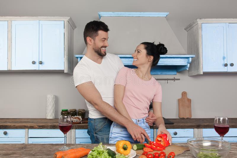Young beautiful couple hugging in the kitchen cooking together a salad. They smile at each other stock photo