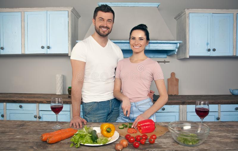 Young beautiful couple in the kitchen cook together a salad. They smile at the camera stock photography
