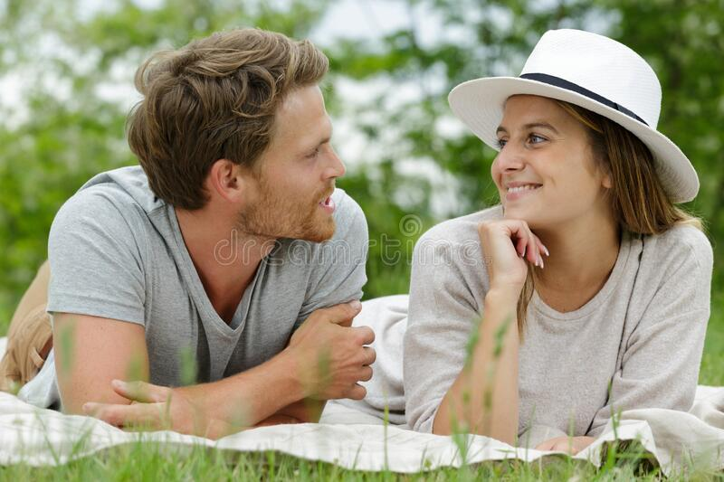 Young beautiful couple laying in spring green meadow stock image