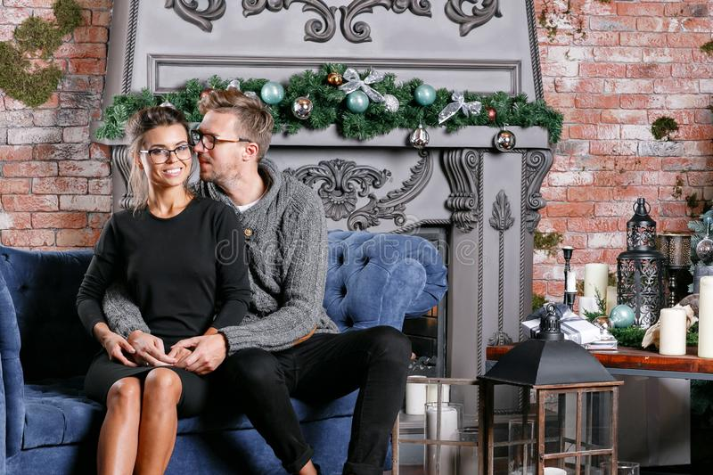 Young beautiful couple In loft room with brick wall. Happy new year. decorated Christmas tree stock image