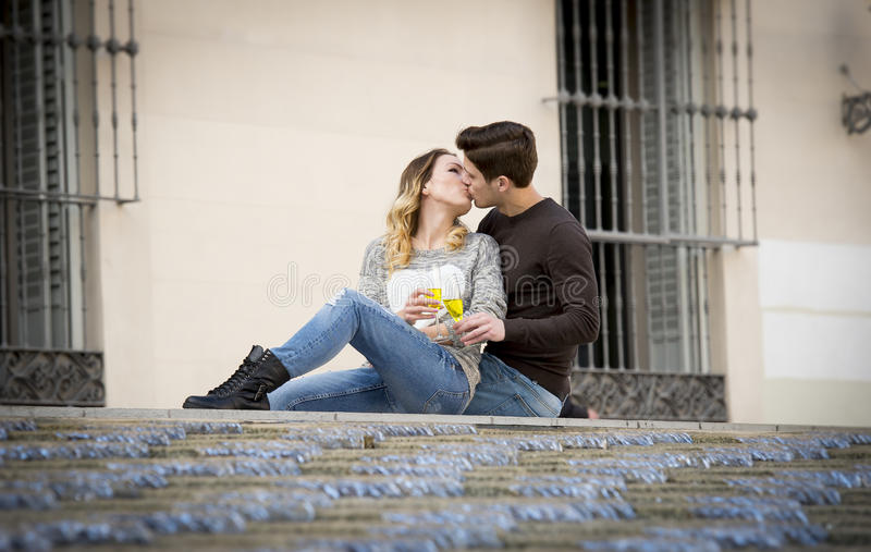 Young beautiful couple in love on street together celebrating Valentines day with Champagne toast. Candid portrait of young beautiful couple in love sitting on royalty free stock image