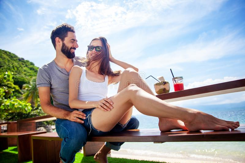 Young beautiful couple in love on the tropical sea in beach cafe royalty free stock photography