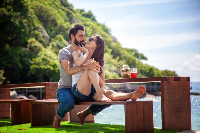 Young beautiful couple in love on the tropical sea in beach cafe stock photo
