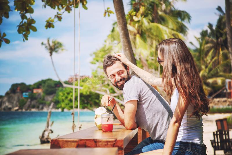 Young beautiful couple in love on the tropical sea in beach cafe, during a honeymoon holiday, Valentine`s Day. Love concept royalty free stock photography