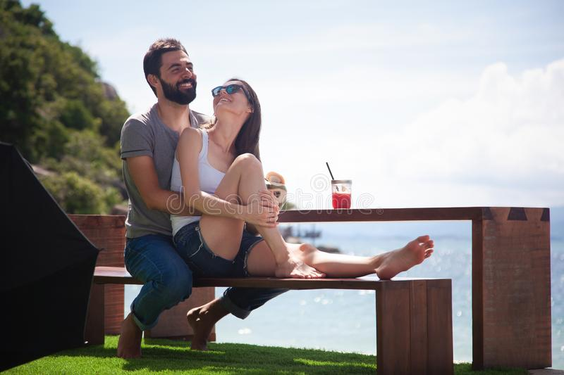Young beautiful couple in love on the tropical sea in beach cafe, royalty free stock image