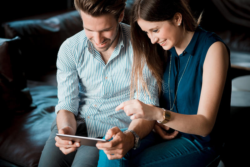 Young beautiful couple lovers. At the cafe using tablet stock photos